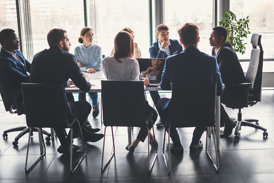 Business Insurance - Group of Employees Sitting in Modern Office During Business Meeting